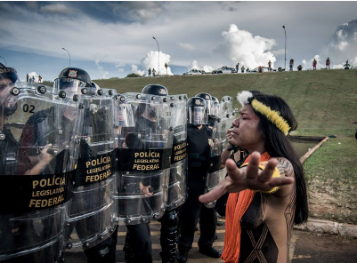 An indigenous woman stands, arms outstretched, in front of a row of riot police.