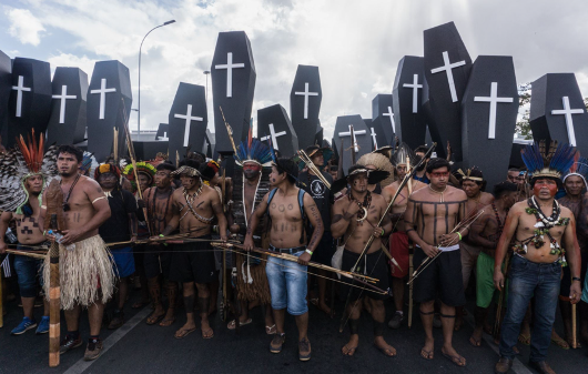 Indigenous protestors stand in a line holding small black coffins with white crosses on them.